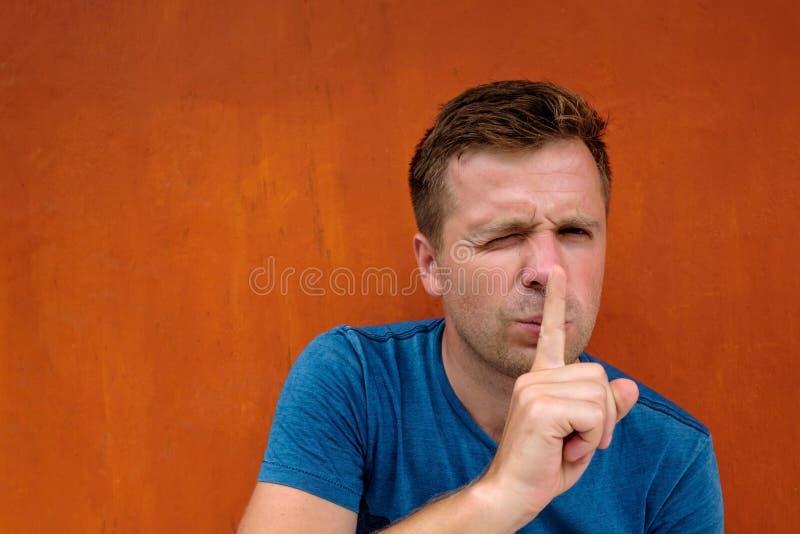 Closeupstående av den unga caucasian mannen som förlägger fingret på kanter som, om för att säga, shh, var tyst royaltyfria foton