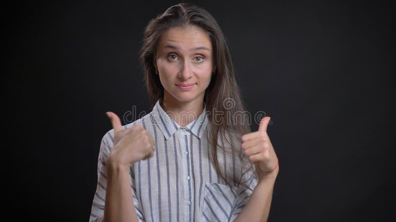 Closeupstående av den unga gulliga caucasian kvinnlign med brunetthår som ser rakt på kameran och visar upp tummar med arkivfoton