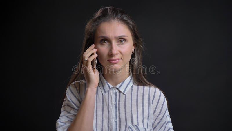 Closeupstående av den unga gulliga caucasian kvinnlign som har en tillfällig konversation telefonen framme av kameran med arkivbilder