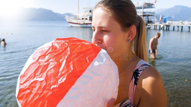 Closeupstående av den unga kvinnan som kämpar för att blåsa upp strandbollen arkivbilder
