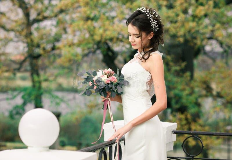Closeupstående av den unga ursnygga bruden Nätt härlig brud med den härliga buketten av blommor som står i balkong av att förbluf royaltyfria foton