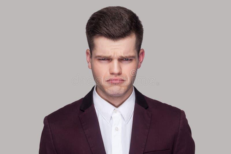 Closeupstående av den uttråkade ledsna stiliga unga mannen i den violetta dräkten royaltyfri fotografi