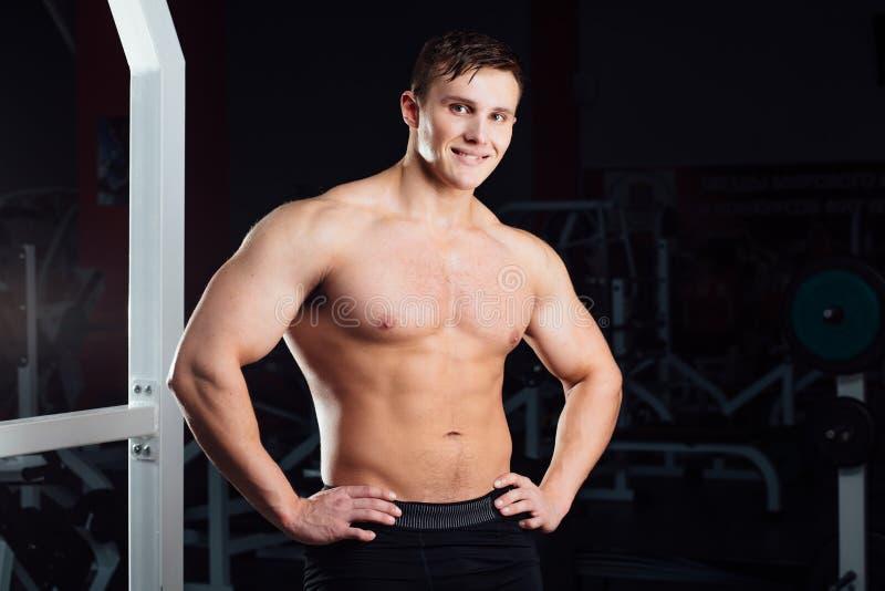 Closeupstående av den yrkesmässiga kroppsbyggaregenomköraren med skivstången på idrottshallen Säker muskulös manutbildning se royaltyfri bild