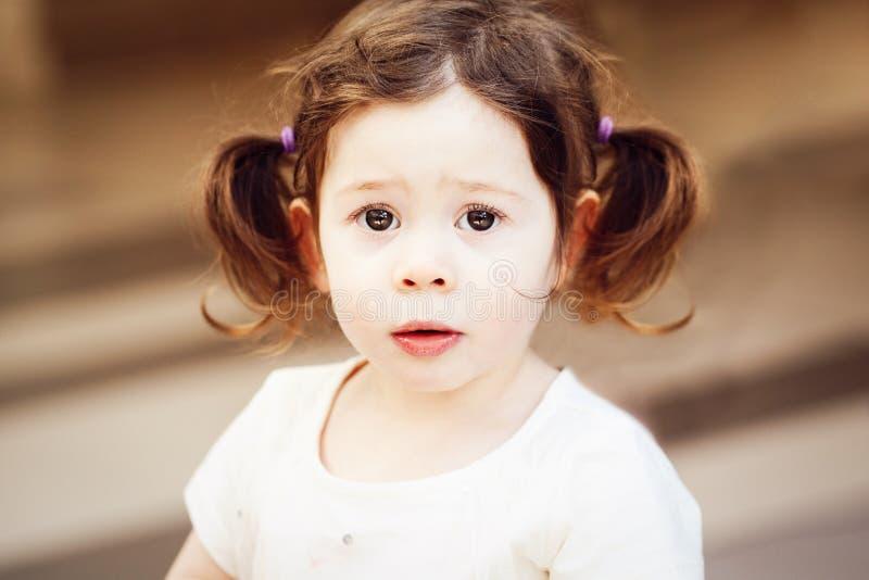Closeupstående av det gulliga förtjusande ledsna upprivna vita Caucasian litet barnflickabarnet med ögon för mörk brunt och locki arkivbilder