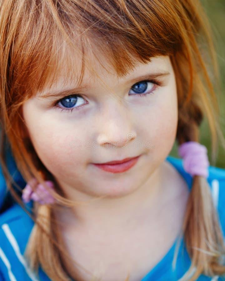 Closeupstående av det gulliga förtjusande lilla rödhåriga Caucasian flickabarnet med blåa ögon arkivfoto
