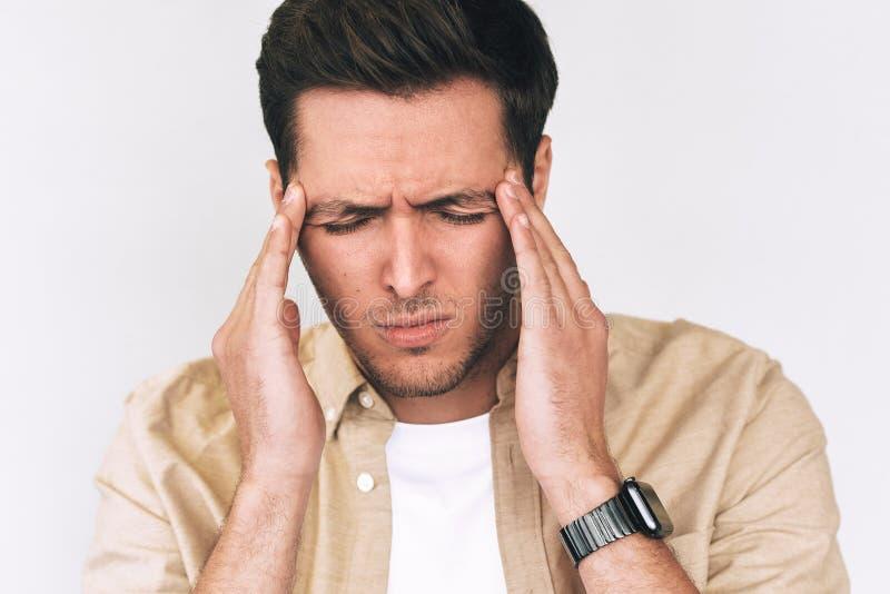 Closeupstående av det ledsna Caucasian anseendet för ung man med stängda ögon som rymmer händer på huvudet som ser stressigt royaltyfri foto