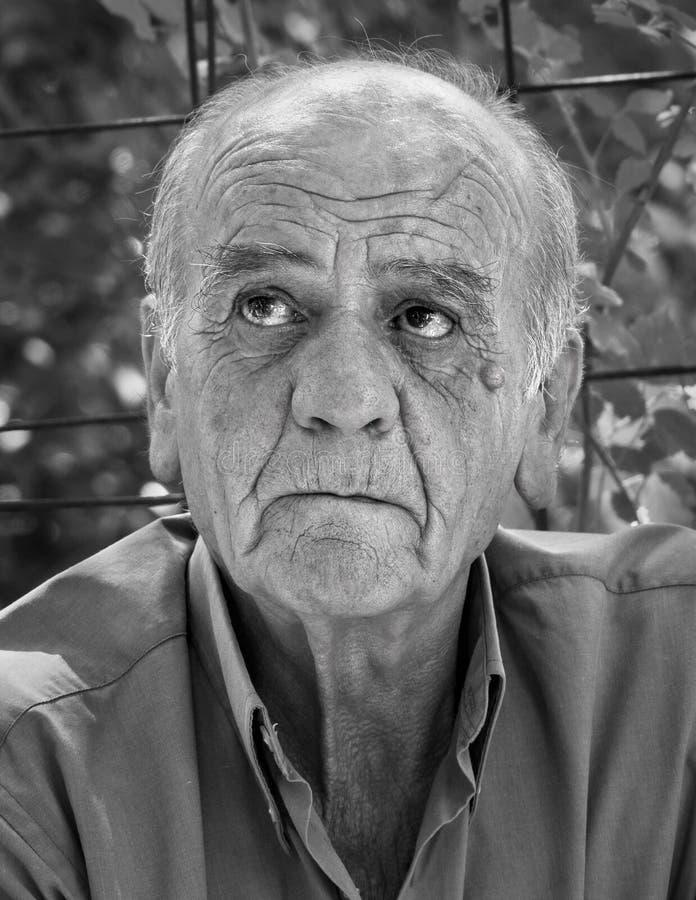 Closeupstående av en allvarlig gammal grekisk pensionerad man, som röker en cigarett med ett leende, i svartvitt royaltyfri foto