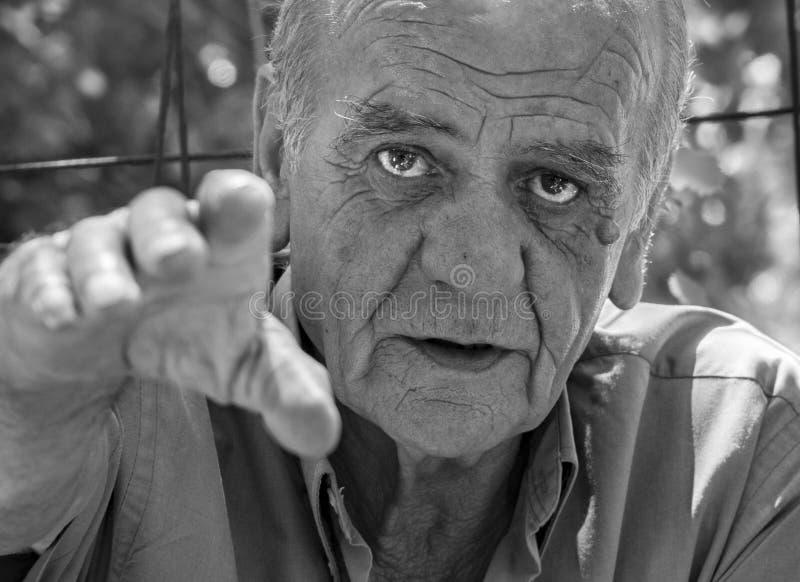 Closeupstående av en allvarlig gammal grekisk pensionerad man, som röker en cigarett med ett leende, i svartvitt arkivbilder