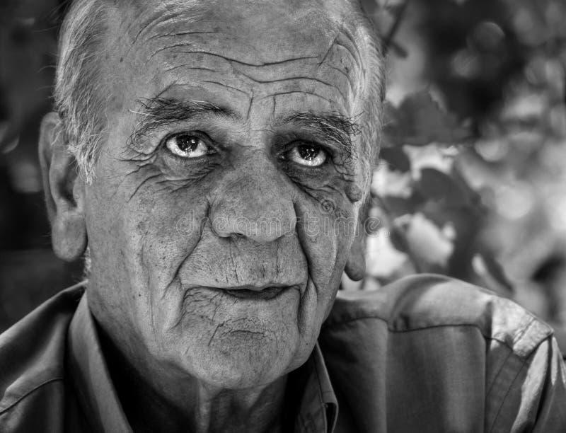 Closeupstående av en allvarlig gammal grekisk pensionerad man, som röker en cigarett med ett leende, i svartvitt arkivfoton
