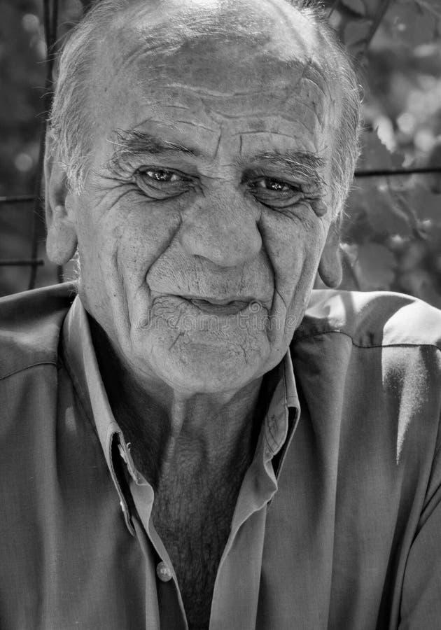 Closeupstående av en allvarlig gammal grekisk pensionerad man, som röker en cigarett med ett leende, i svartvitt fotografering för bildbyråer