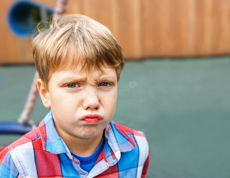 Closeupstående av en behandla som ett barnpojke som gör en rolig framsida royaltyfri foto