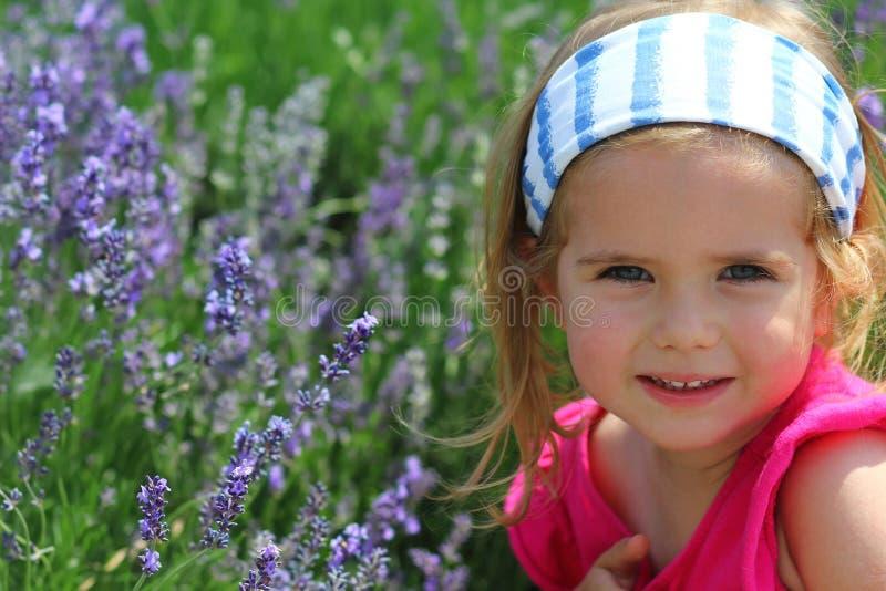 Closeupstående av en gullig litet barnflicka som tycker om lavendelfieldl royaltyfri foto