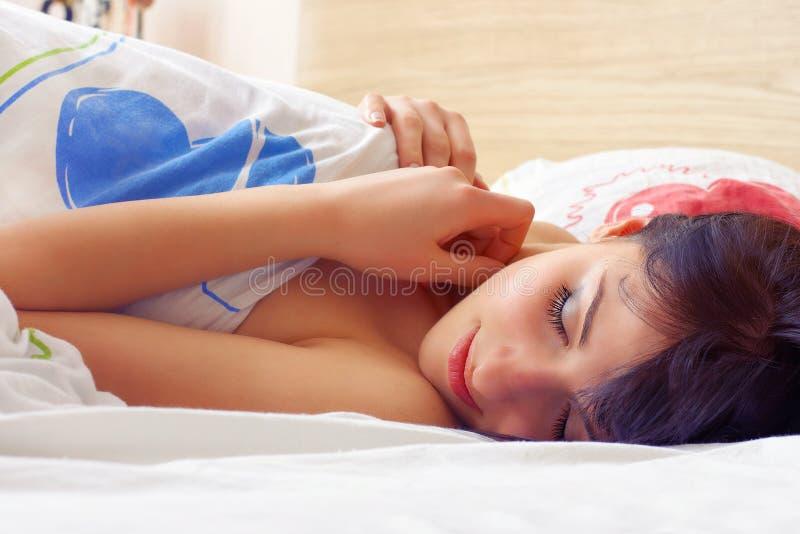 Closeupstående av en gullig ung kvinna som sover på sängen royaltyfria foton