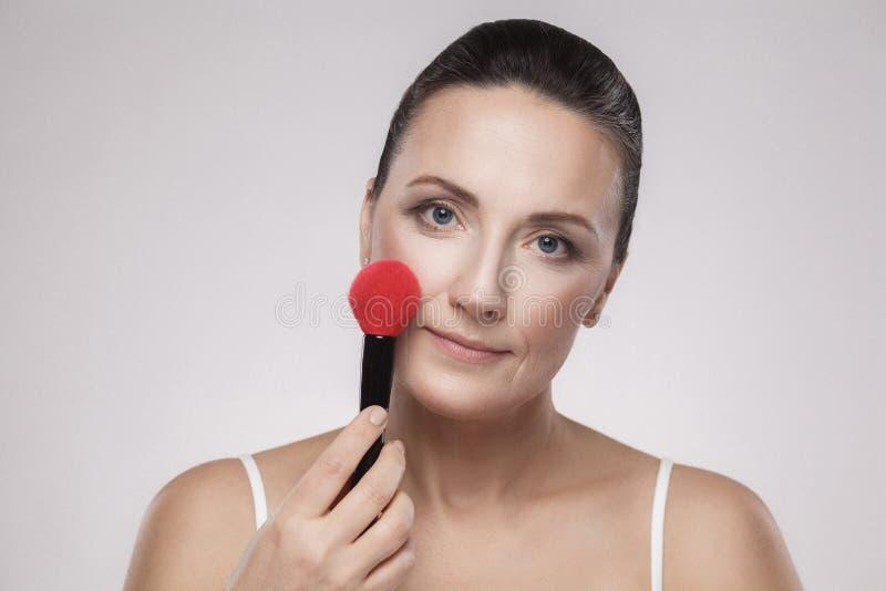 Closeupstående av en härlig mellersta åldrig kvinna som applicerar det torra kosmetiska tonala fundamentet på framsidan genom att arkivbilder