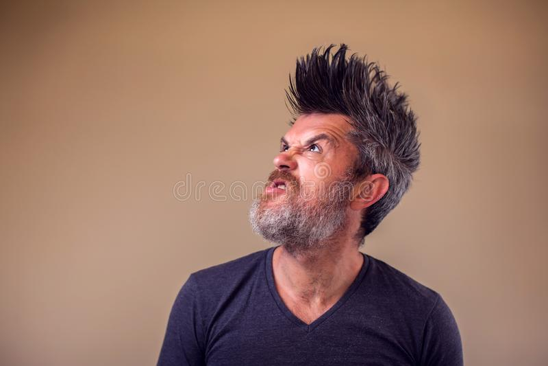 Closeupstående av en ilsken vuxen man med ett skägg och iroquoisen arkivfoto
