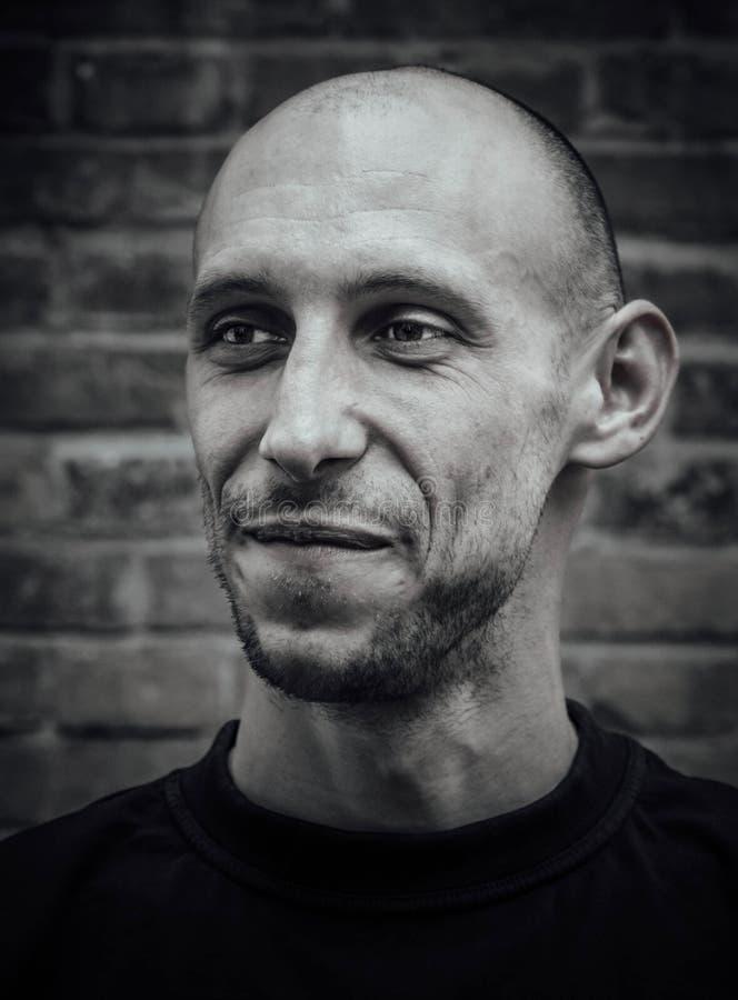 Closeupstående av en skallig man med ett leende och ett brutalt utseende i svartvitt royaltyfri fotografi