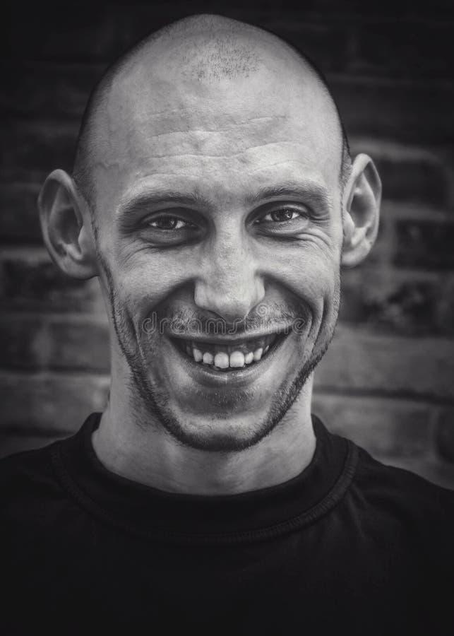 Closeupstående av en skallig man med ett leende och ett brutalt utseende i svartvitt royaltyfria bilder