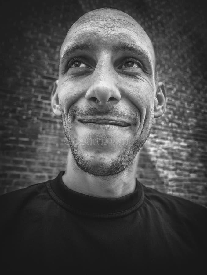 Closeupstående av en skallig man med ett leende och ett brutalt utseende i svartvitt arkivbilder