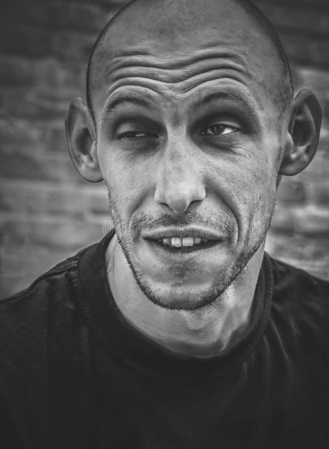 Closeupstående av en skallig man med ett leende och ett brutalt utseende i svartvitt arkivfoton