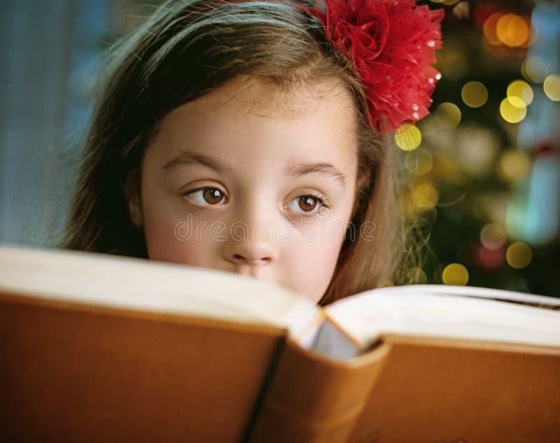 Closeupstående av ett gulligt, liten flicka som läser en bok arkivfoto