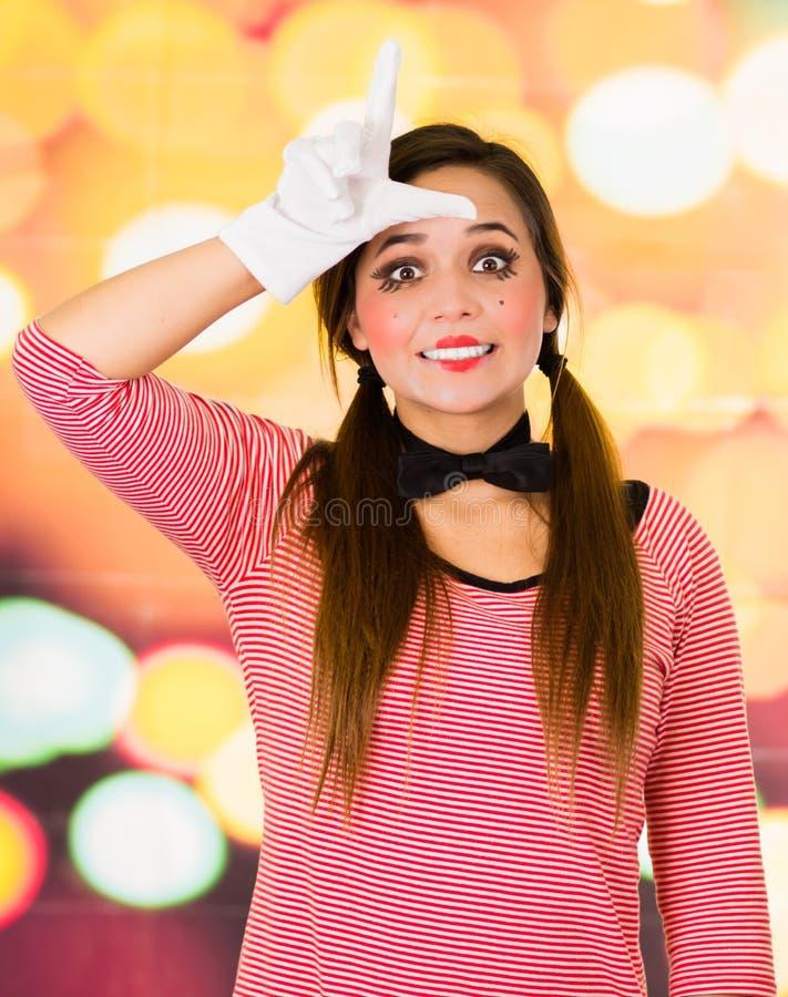 Closeupstående av kvinnlig clownfars som gör en gest förloraren med fingrar arkivfoto