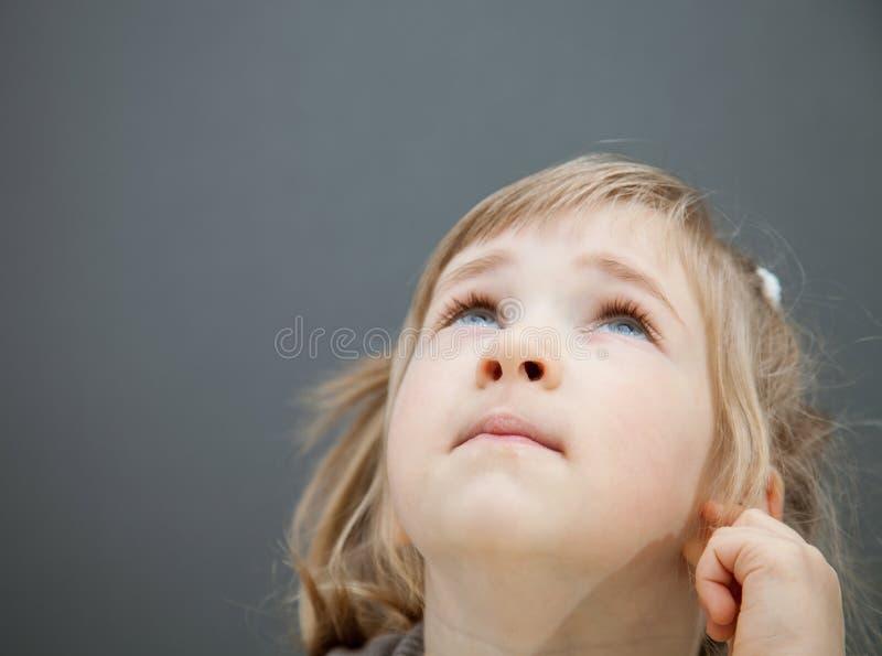 Closeupstående av lite flickan som ser upp arkivfoto