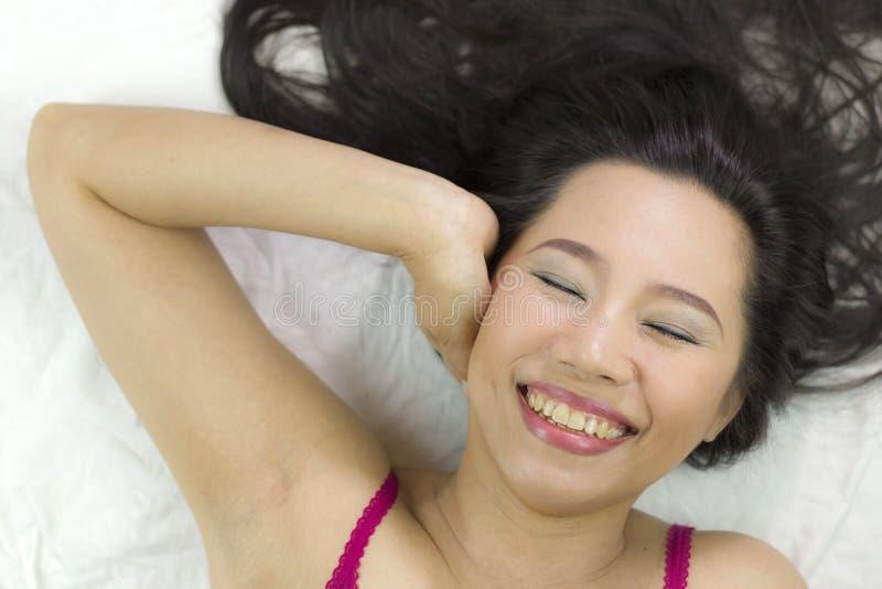 Closeupstående av lyckliga asiatiska kvinnor som ligger på jordning med svart långt hår tillförordnat leende, gyckel arkivbilder