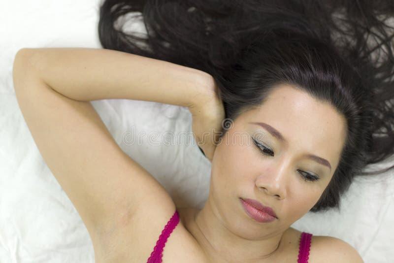Closeupstående av lynniga asiatiska kvinnor som ligger på jordning med svart långt hår agera som är upprivet, olyckligt royaltyfria bilder