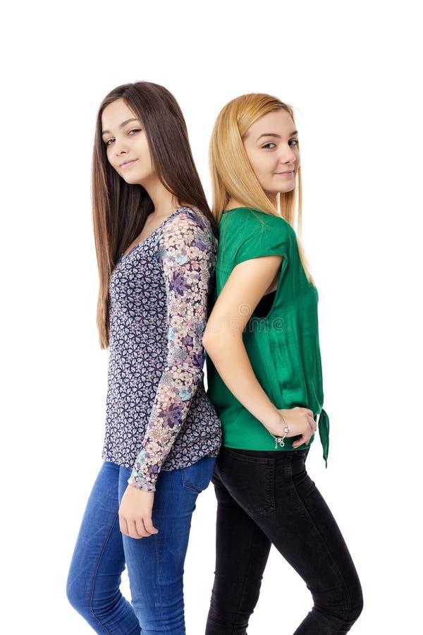 Closeupstående av två stående tonårs- flickor tillbaka som ska dras tillbaka fotografering för bildbyråer