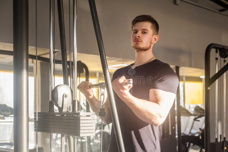 Closeupstående av ung vuxen utbildning för sportidrottsman nenman på idrottshallen bara som står och lyfter vikter i idrottshalle arkivfoto