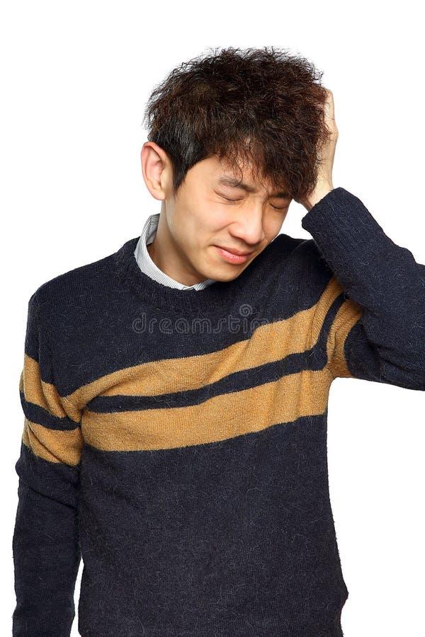 Closeupstående, stressad ung asiatisk man, händer på huvudet med b arkivbild