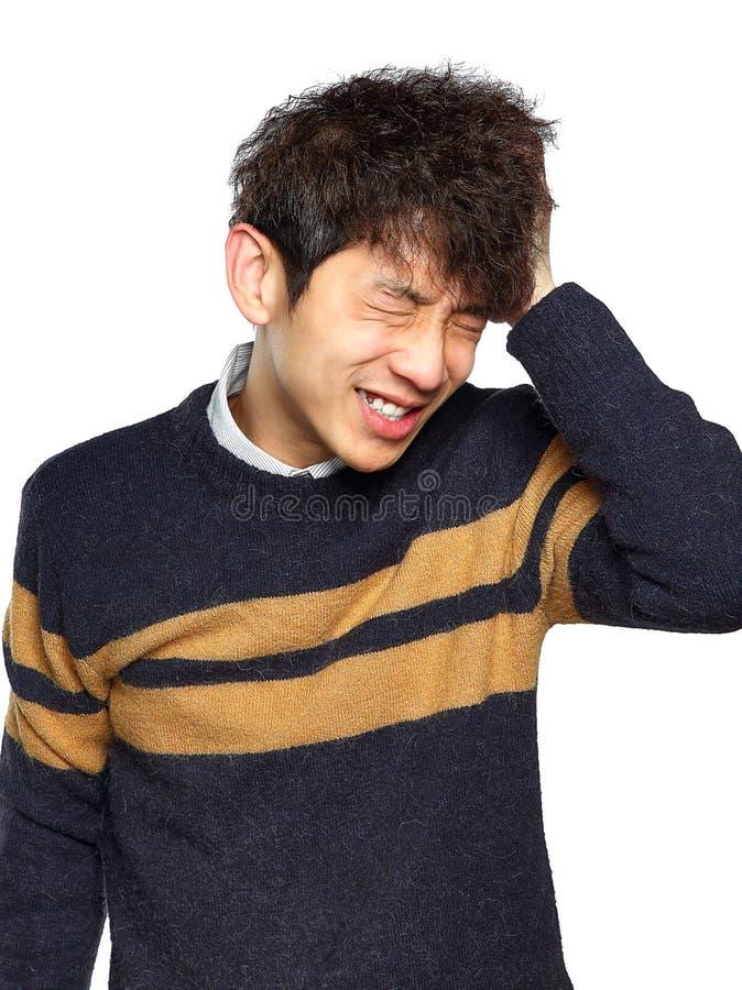 Closeupstående, stressad ung asiatisk man, händer på huvudet med b royaltyfri fotografi