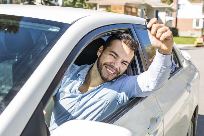 Closeupstående, ungt gladlynt, glat som ler, män som upp rymmer tangenter till hennes första nya bil royaltyfri bild