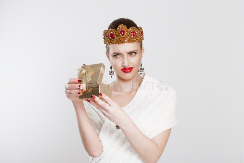 Closeupståendemitt åldrades kvinnan öppningsgåva somasken förargar mycket på vad hon mottog, isolerad vit bakgrund Negativ m?nnis royaltyfri bild
