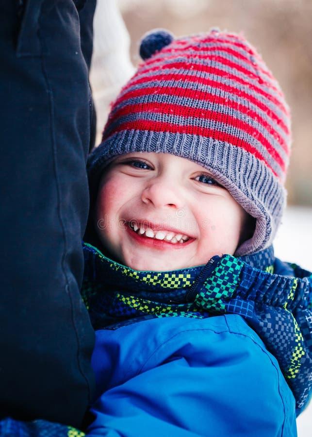 Closeupståenden av att le det skratta Caucasian vita litet barnpojkebarnet i vinterkläder som kramar hans moder, uppfostrar utanf arkivfoto