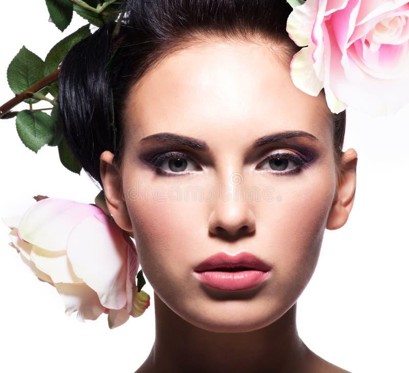 Closeupståenden av den härliga kvinnan med rosa färger blommar i hår arkivfoton