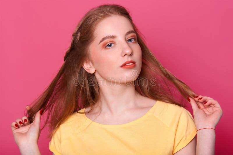 Closeupståenden av den härliga unga kvinnan rymmer hennes raka långa skinande bruna hår Bär ljus makeup för attraktiv flickawitn, arkivbild