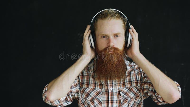 Closeupståenden av den skäggiga unga mannen i hörlurar lyssnar till musik och att se in i att le för kamera royaltyfri fotografi
