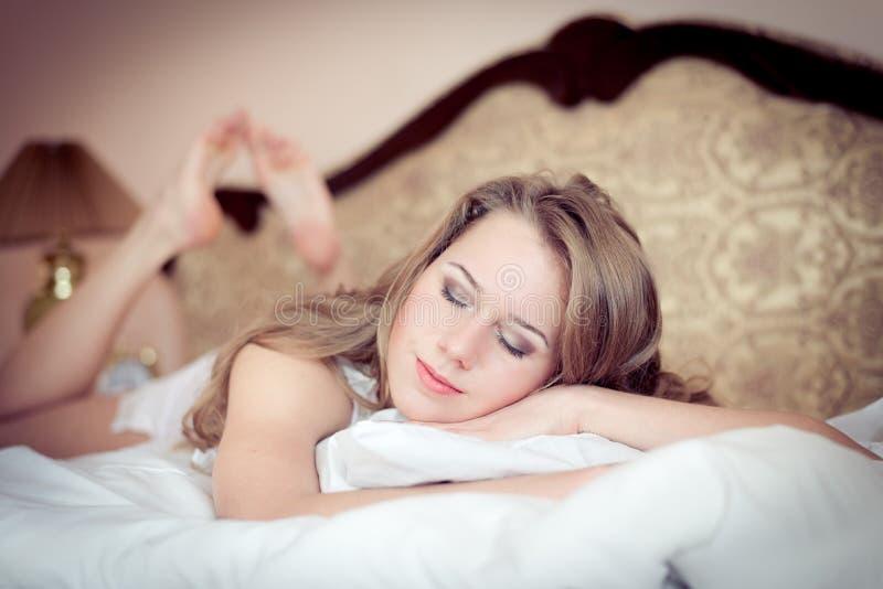 Closeupståenden av den unga härliga kvinnan som har roligt koppla av, synar stängt ligga i pyjamas på den vita sängen arkivbild