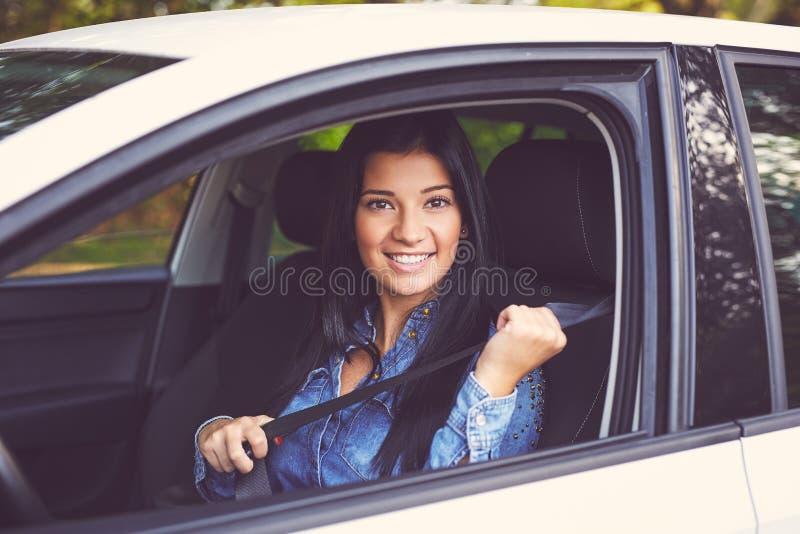 Closeupståenden av den unga kvinnan fäster säkerhetsbältet arkivfoton