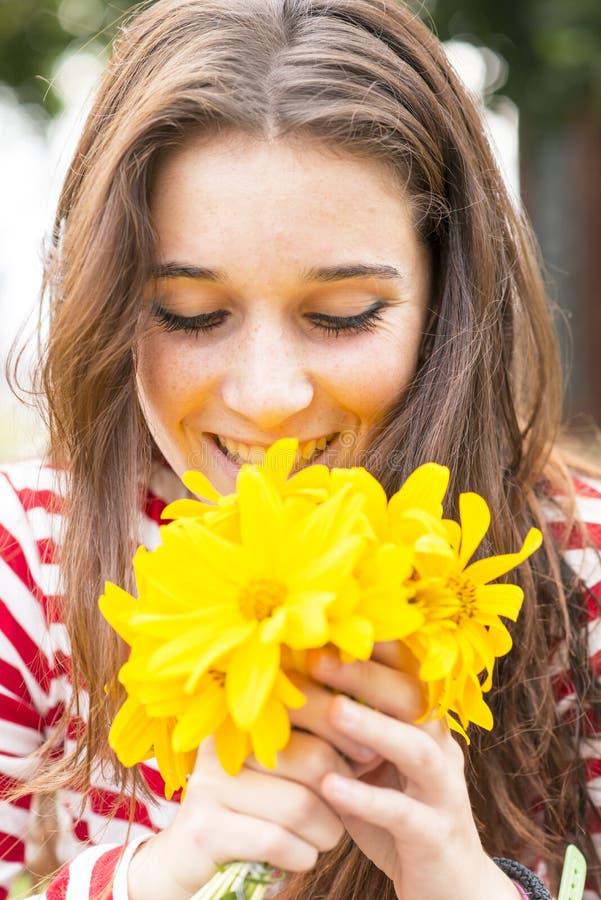 Closeupståenden av det lyckliga kvinnainnehavet blommar buketten royaltyfri foto