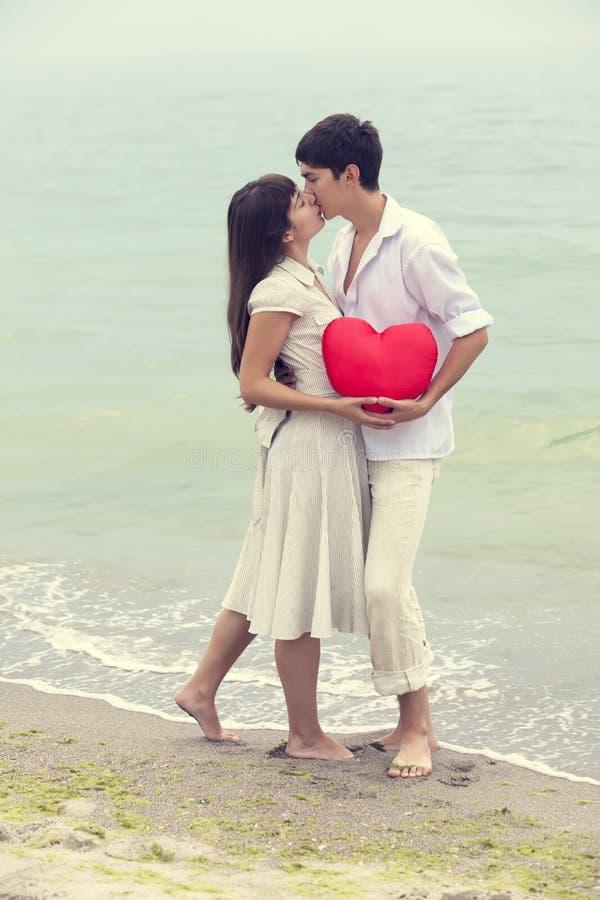 Closeupståenden av lyckligt kopplar ihop på stranden med hjärta. fotografering för bildbyråer