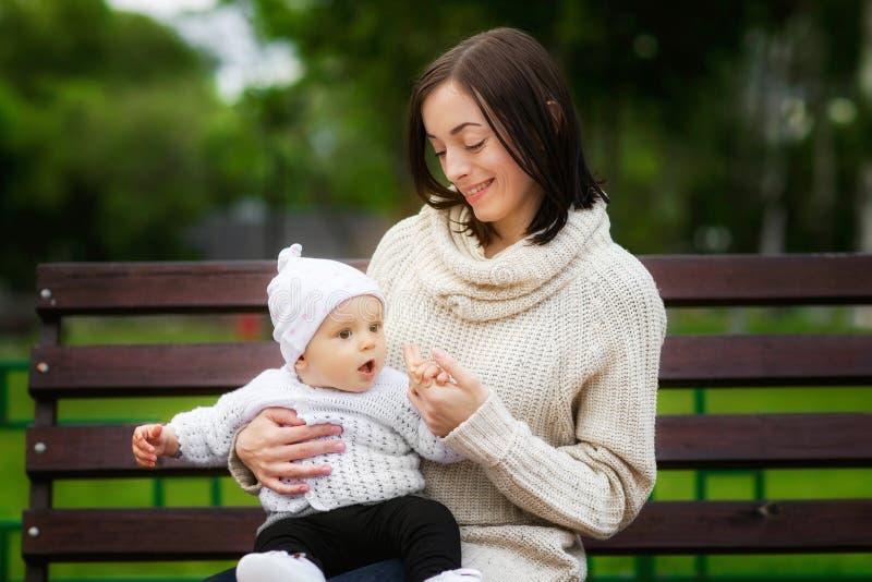 Closeupståenden av mamman som spelar med, behandla som ett barn på bänken på parkerar utomhus bakgrund arkivbild