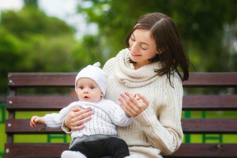 Closeupståenden av mamman som spelar med, behandla som ett barn utomhus på bänken på p royaltyfri foto