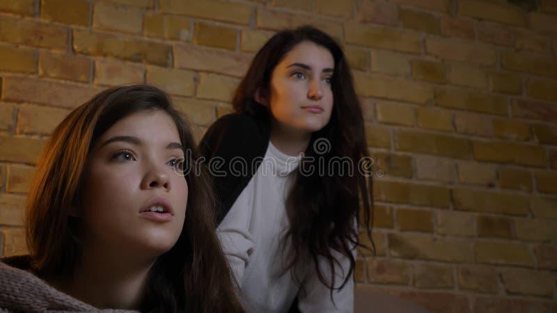 Closeupståenden av två unga gulliga flickor som håller ögonen på witn för TV, upphetsade tillsammans ansiktsuttryck arkivfoto