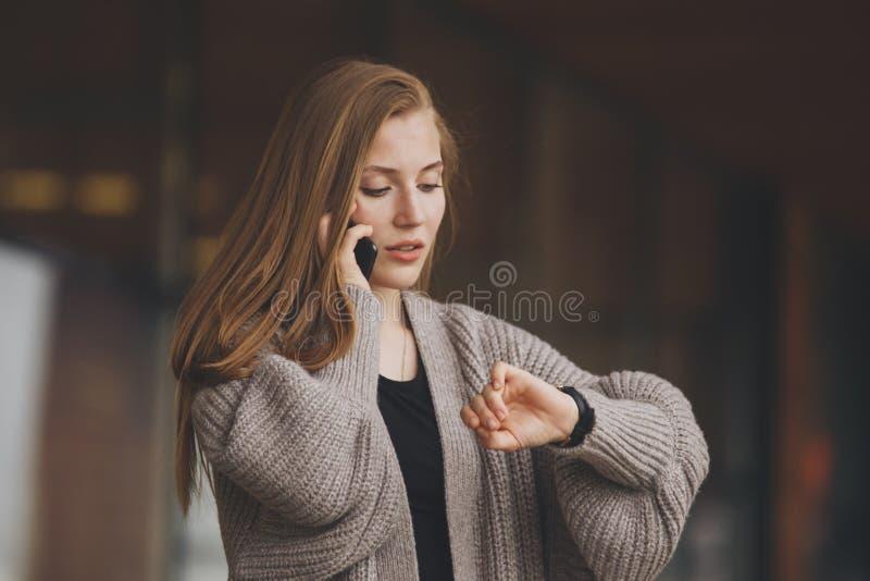 Closeupståenden, den unga kvinnan i grå blazer för affärsdräkt som talar på mobiltelefonen, angick om spring ut ur tid på royaltyfri fotografi