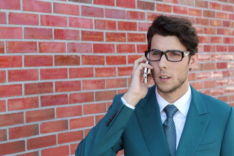 Closeupståenden, den unga mannen förargade, frustrerade, skitförbannat av någon som lyssnar på hans mobiltelefon, dåliga nyheter, arkivfoto