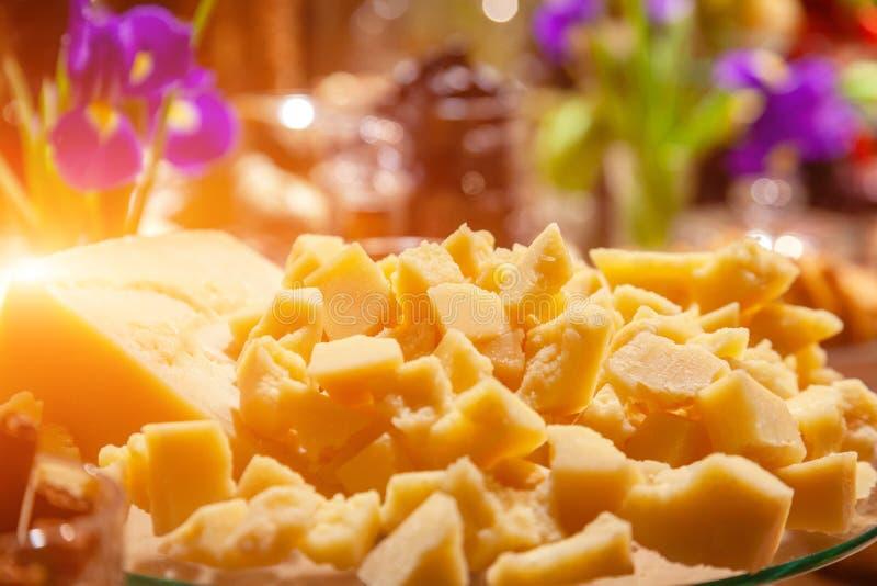 Closeupstycken av italiensk hårdostparmesan på banguet Begreppsavsmakning på ostfabriken som sköter om, presentation i blomma arkivbilder