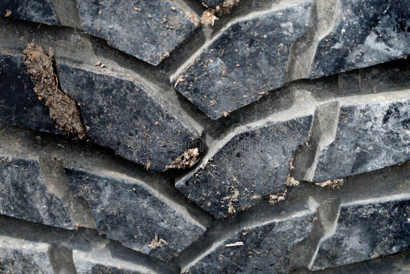 Closeupsvartgummihjulet av av vägbilen har smutsig jord fotografering för bildbyråer