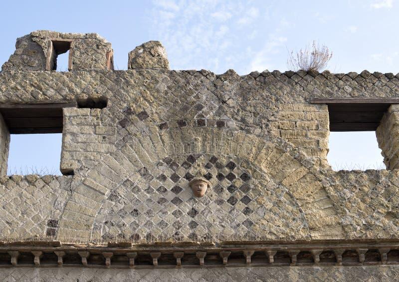 Closeuptegelplatta och utvändig vägg för framsida av ett hus i Parco Archeologico di Ercolano royaltyfria bilder